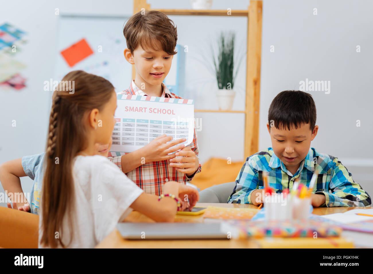 Écolier attentif expliquant de nouveau matériel pour les partenaires Photo Stock
