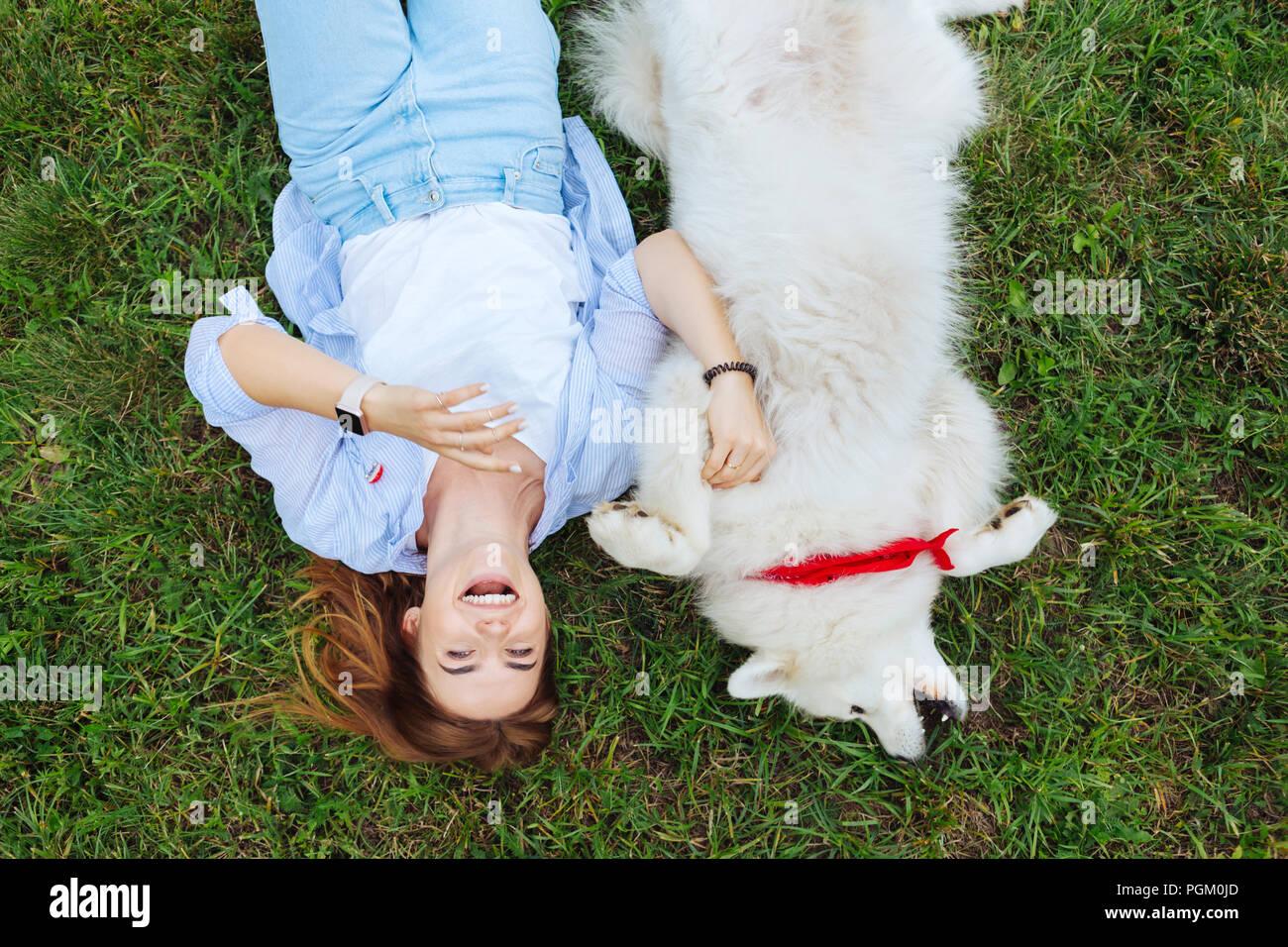 Drôle de femme en riant tout en jouant avec son chien blanc Photo Stock