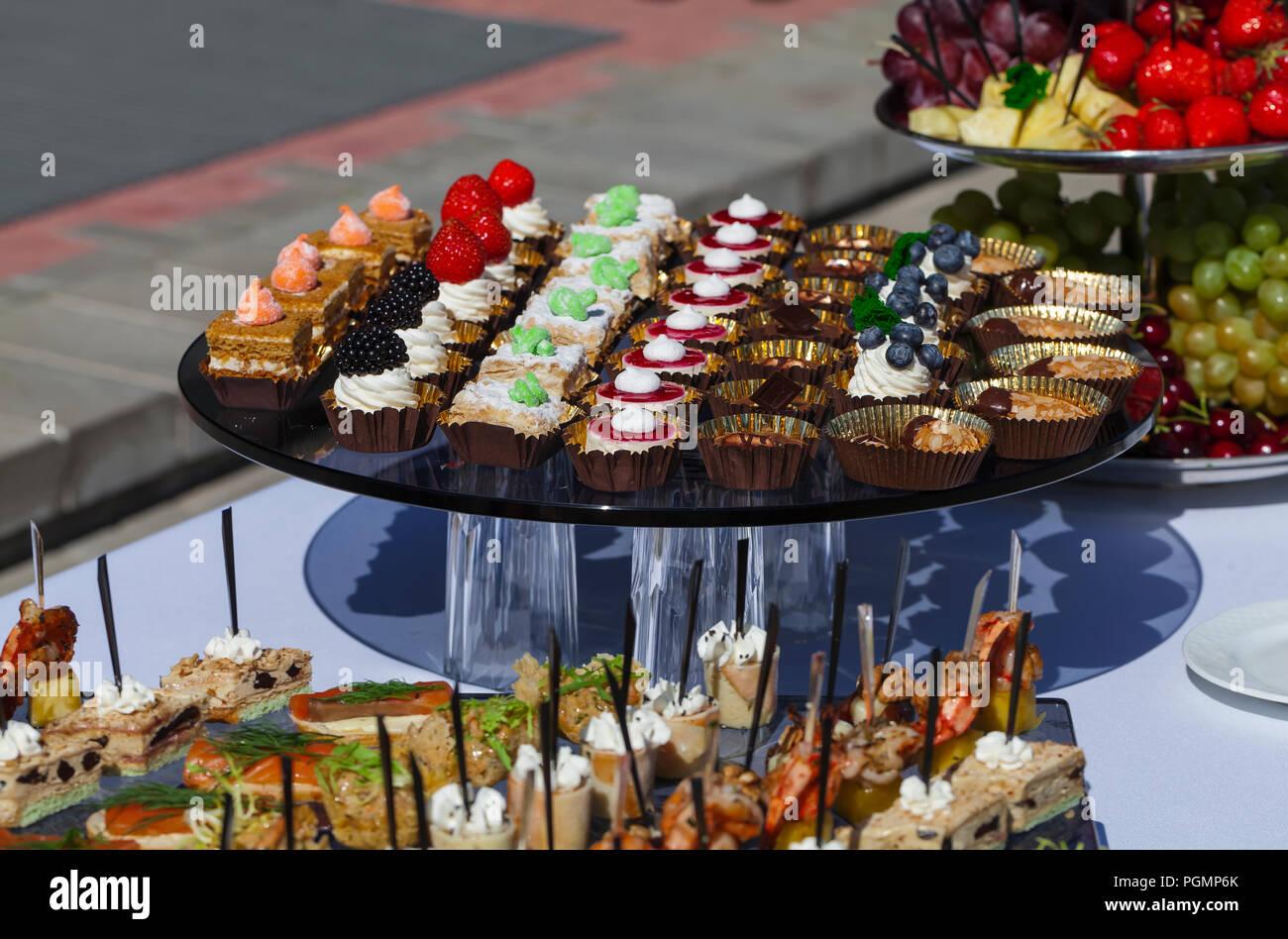 Service traiteur . sandwichs viande, poisson, légumes canapés sur une table de mariage fête piscine Photo Stock