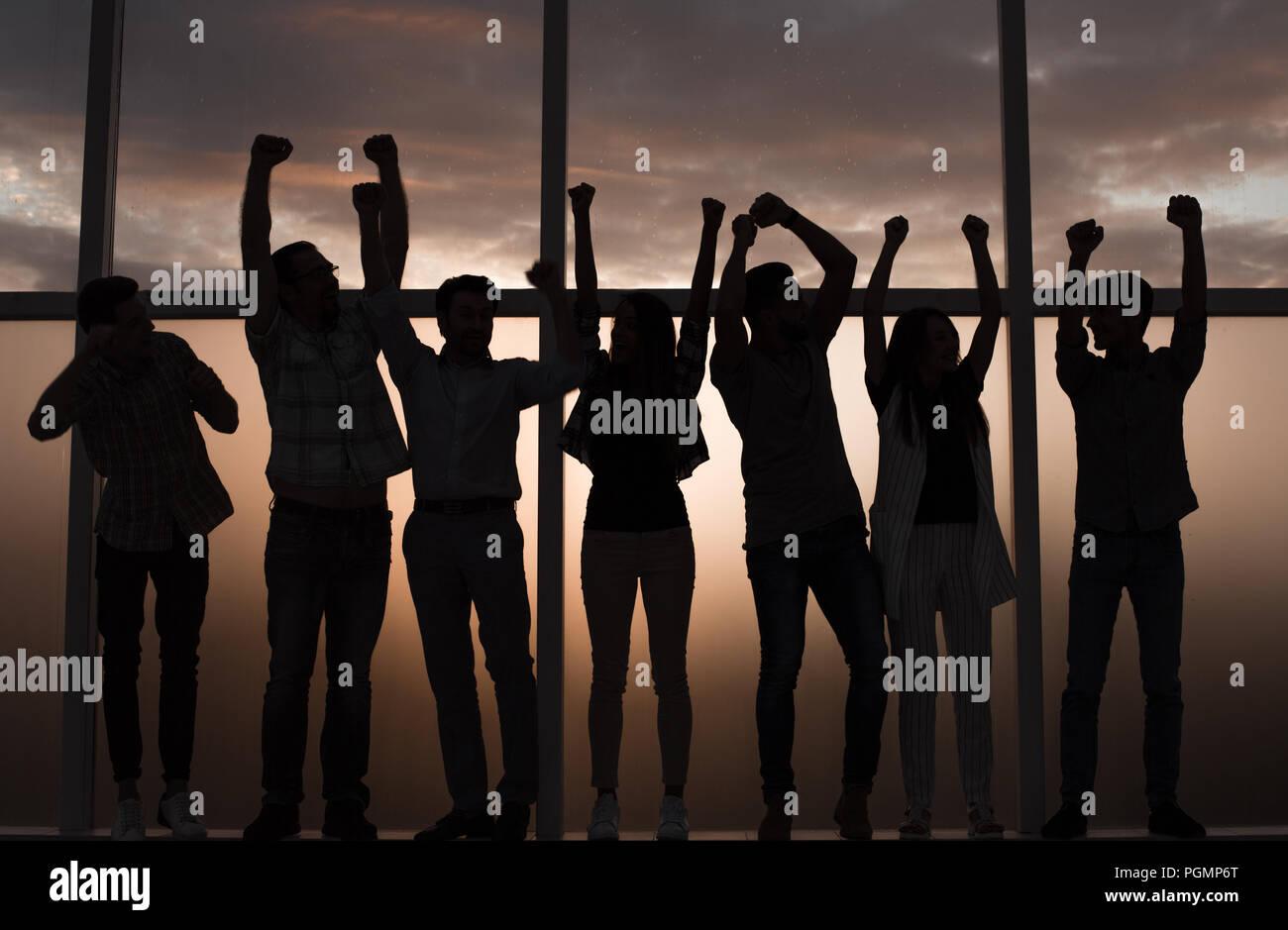 Business team standing près de la fenêtre avec les mains en l'air Photo Stock