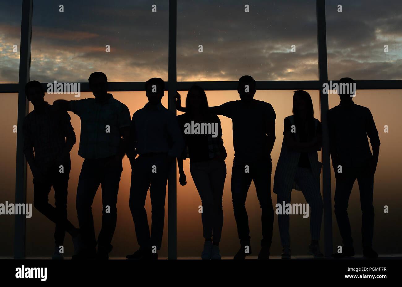 Business team standing près de la fenêtre, le soir, sombre Photo Stock