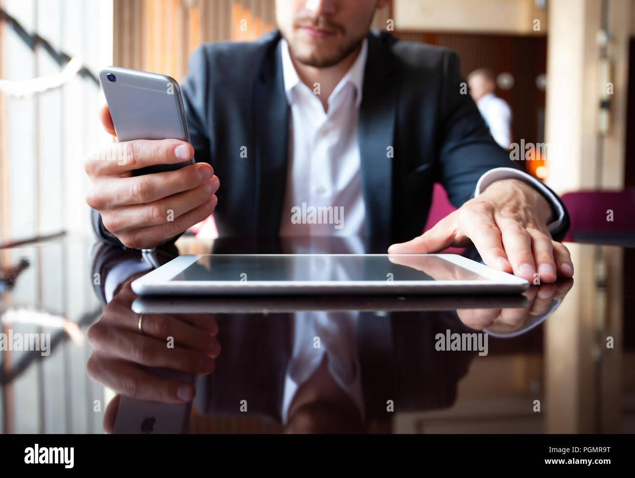Jeune homme d'affaires travaillant avec les appareils modernes, tablette numérique, ordinateur et téléphone mobile. Photo Stock