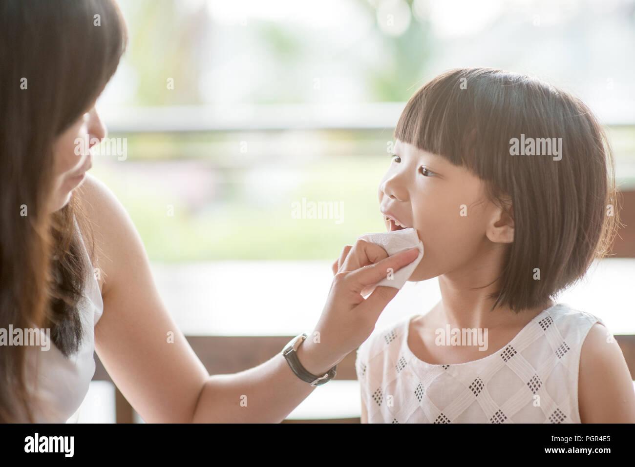 Maman bouche lingettes pour son enfant au café. Vie de plein air famille asiatique avec lumière naturelle. Banque D'Images