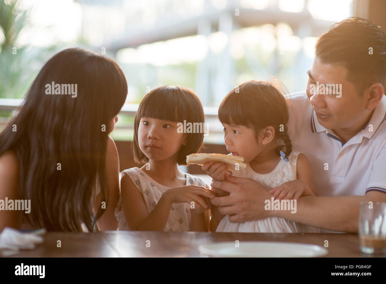 Heureux les enfants de manger et le partage d'toast au beurre au café. Vie de plein air famille asiatique avec lumière naturelle. Photo Stock