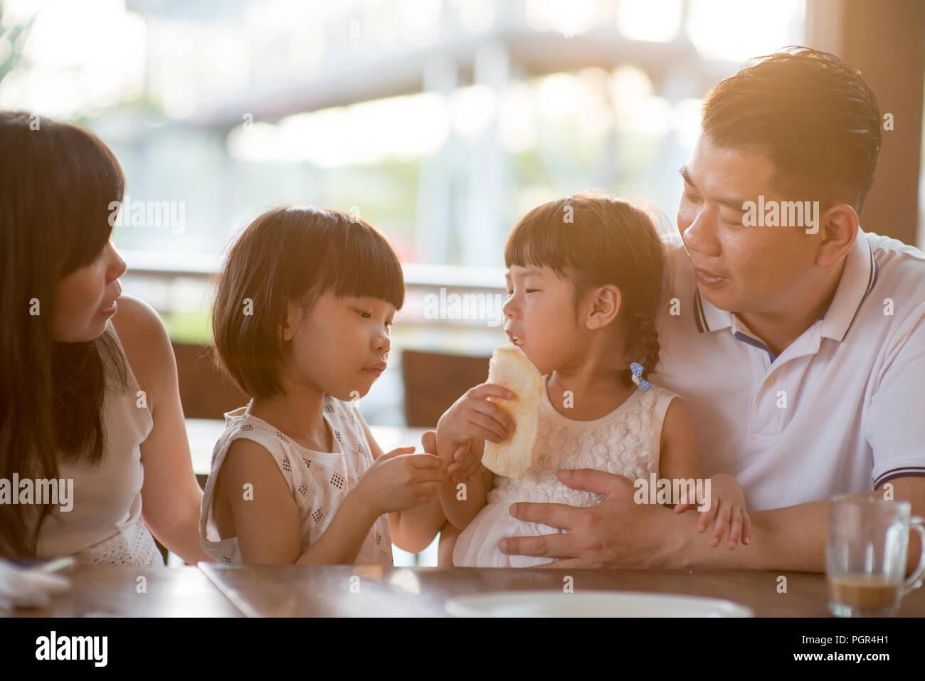 Enfants mignons et manger du pain partage au cafétéria. Vie de plein air famille asiatique avec lumière naturelle. Photo Stock