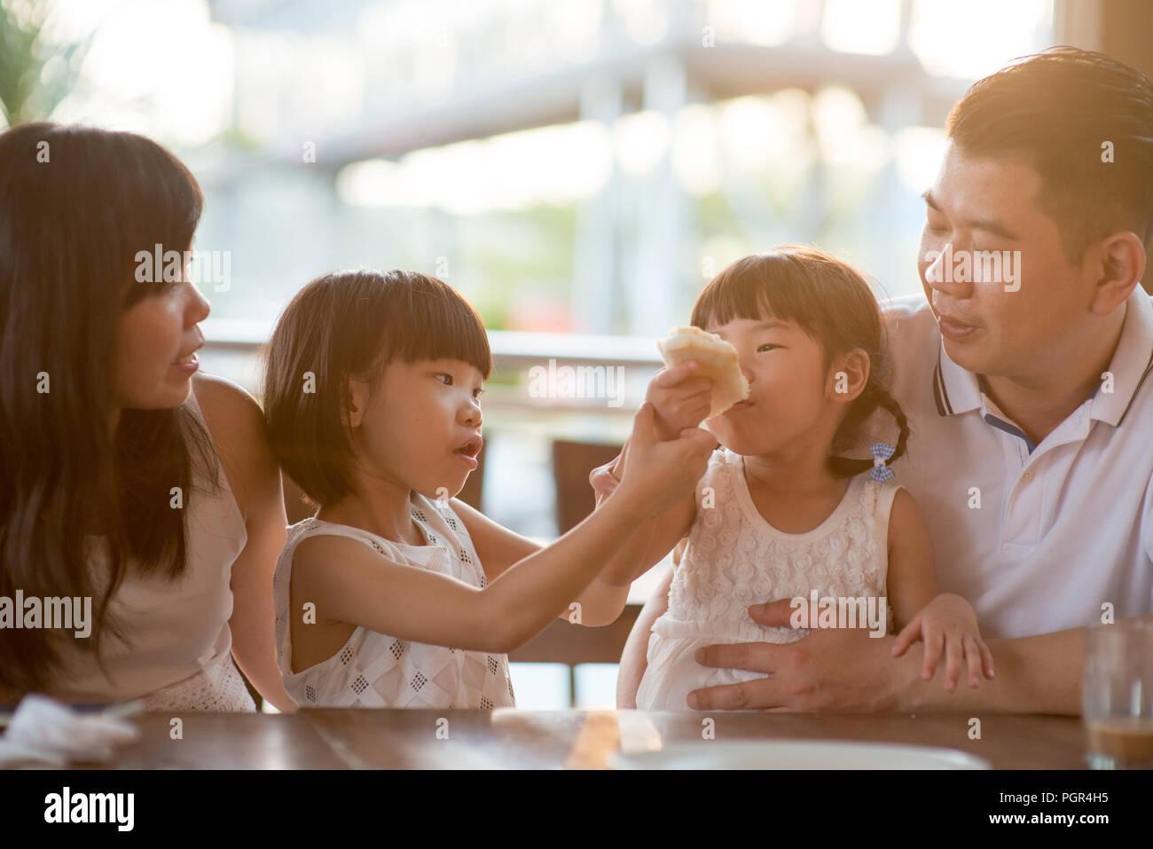 Adorables enfants alimentation et toast au beurre de partage à la cafétéria. Vie de plein air famille asiatique avec lumière naturelle. Photo Stock