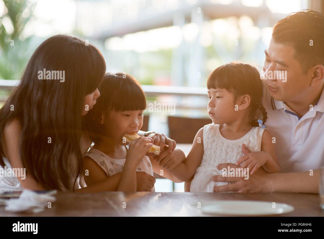 L'alimentation des enfants et le partage du pain pour le cafétéria. Vie de plein air famille asiatique avec lumière naturelle. Photo Stock
