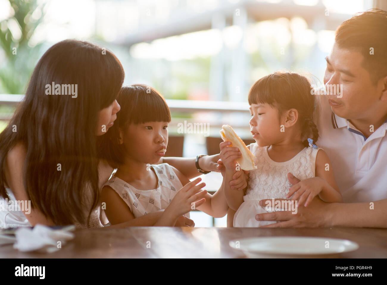 Heureux les enfants de manger et de partager le pain dans une cafétéria. Vie de plein air famille asiatique avec lumière naturelle. Photo Stock