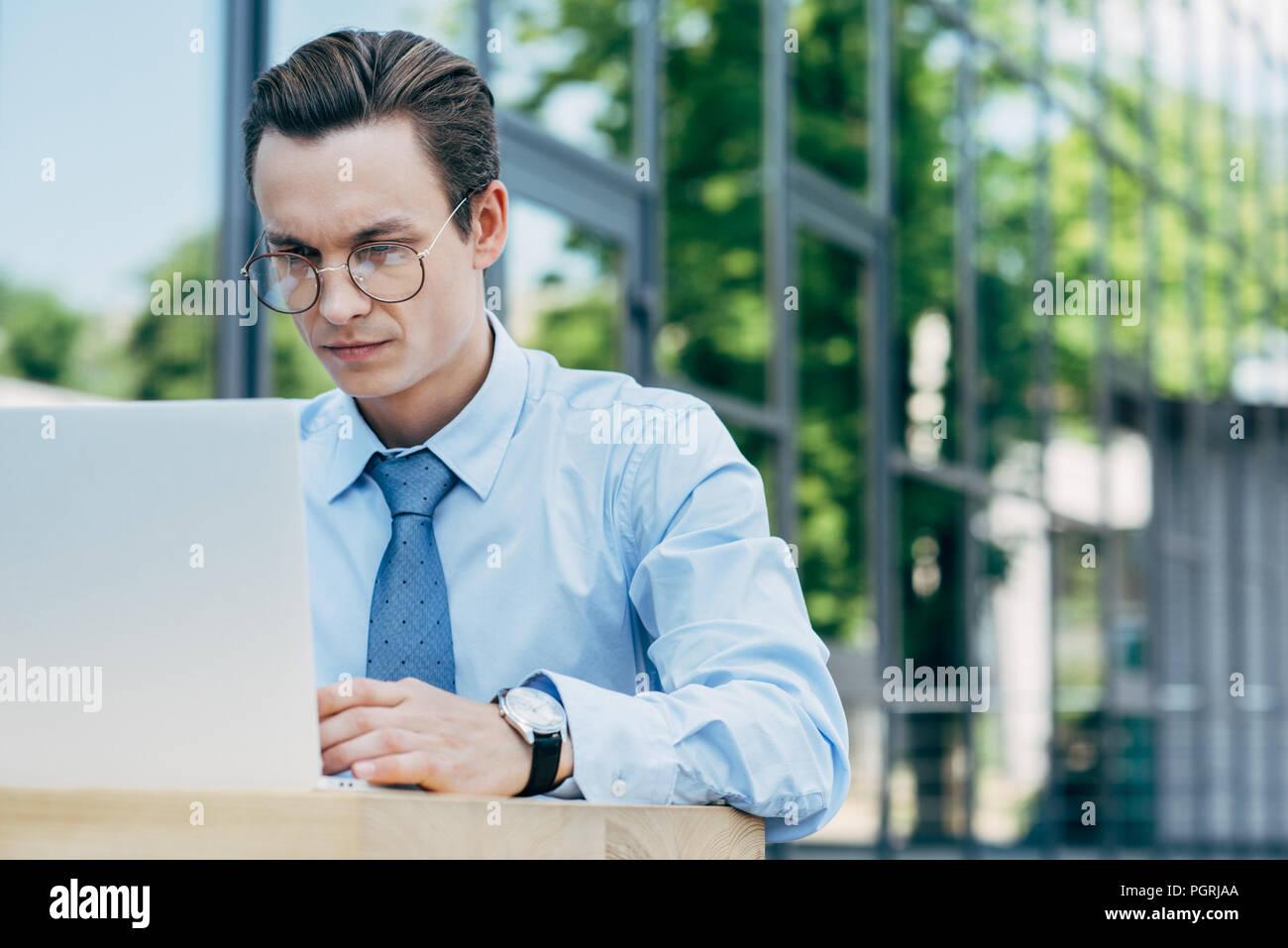 Beau jeune homme d'ordinateur portable à l'aide de lunettes à l'extérieur du bâtiment moderne Banque D'Images