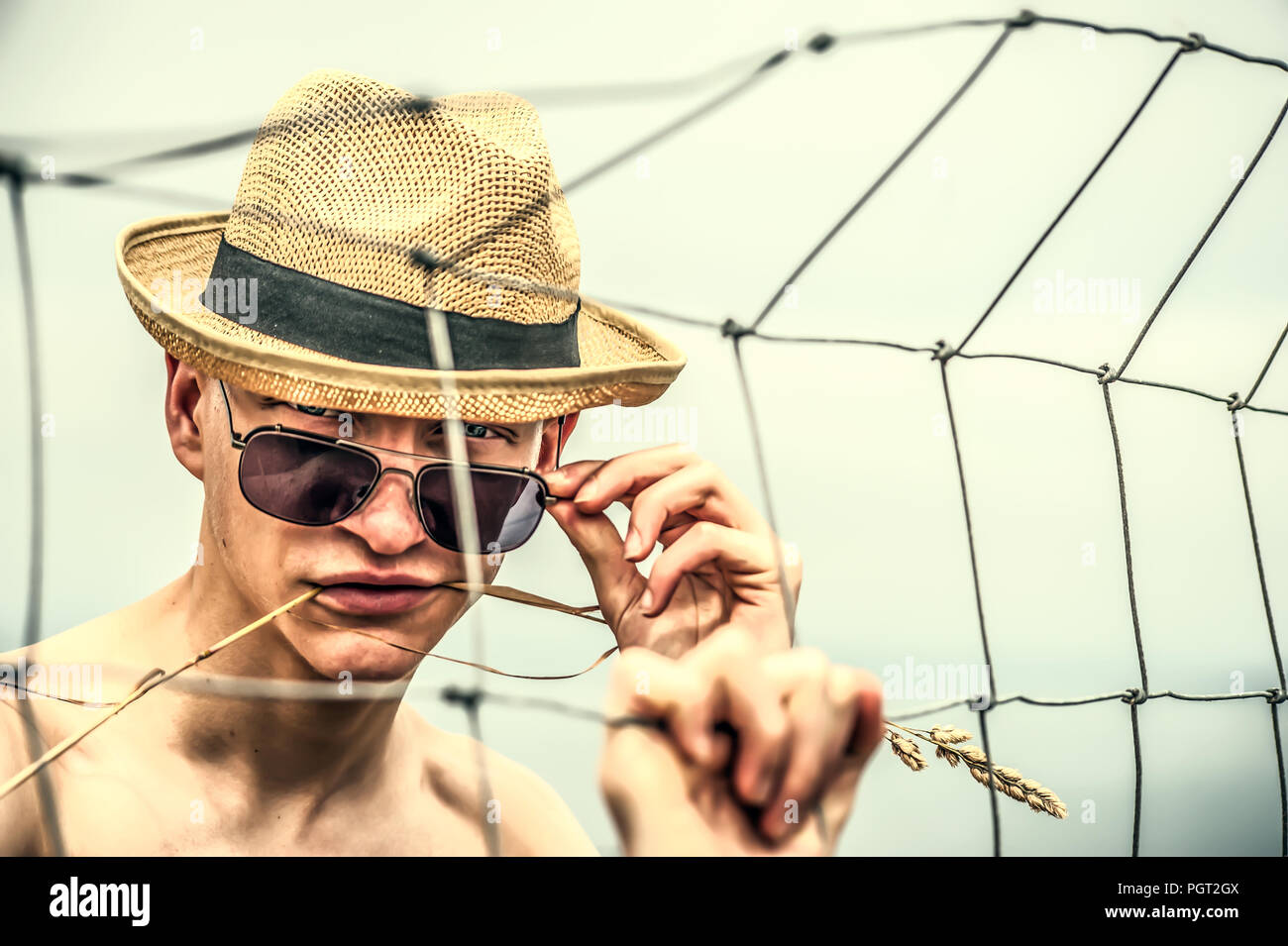 Young man wearing straw hat standing dans les champs Banque D'Images