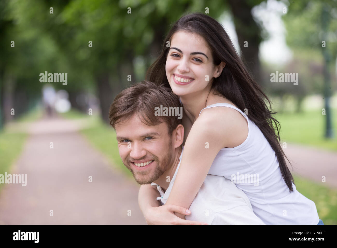 Portrait of smiling young girlfriend piggyback millennial boyfri Photo Stock