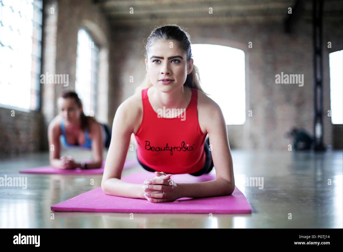 Belles femmes bénéficiant de l'Aérobic sur salle de sport, d'entraînement sur les femmes avant la formation gym mat Photo Stock