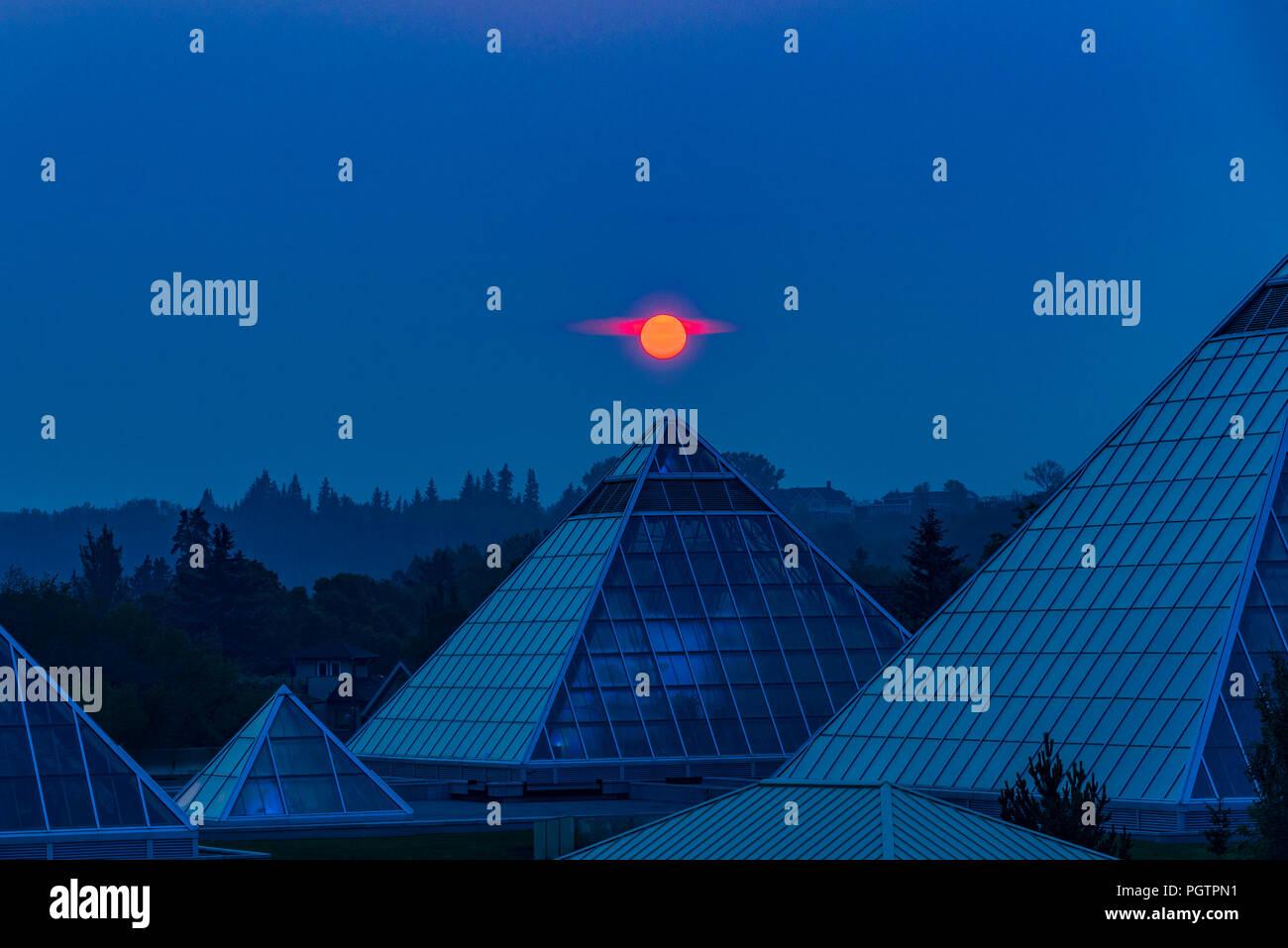 Soleil se lève à travers la fumée rempli ciel, Muttart Conservatory Pyramids, Edmonton, Alberta, Canada. Photo Stock