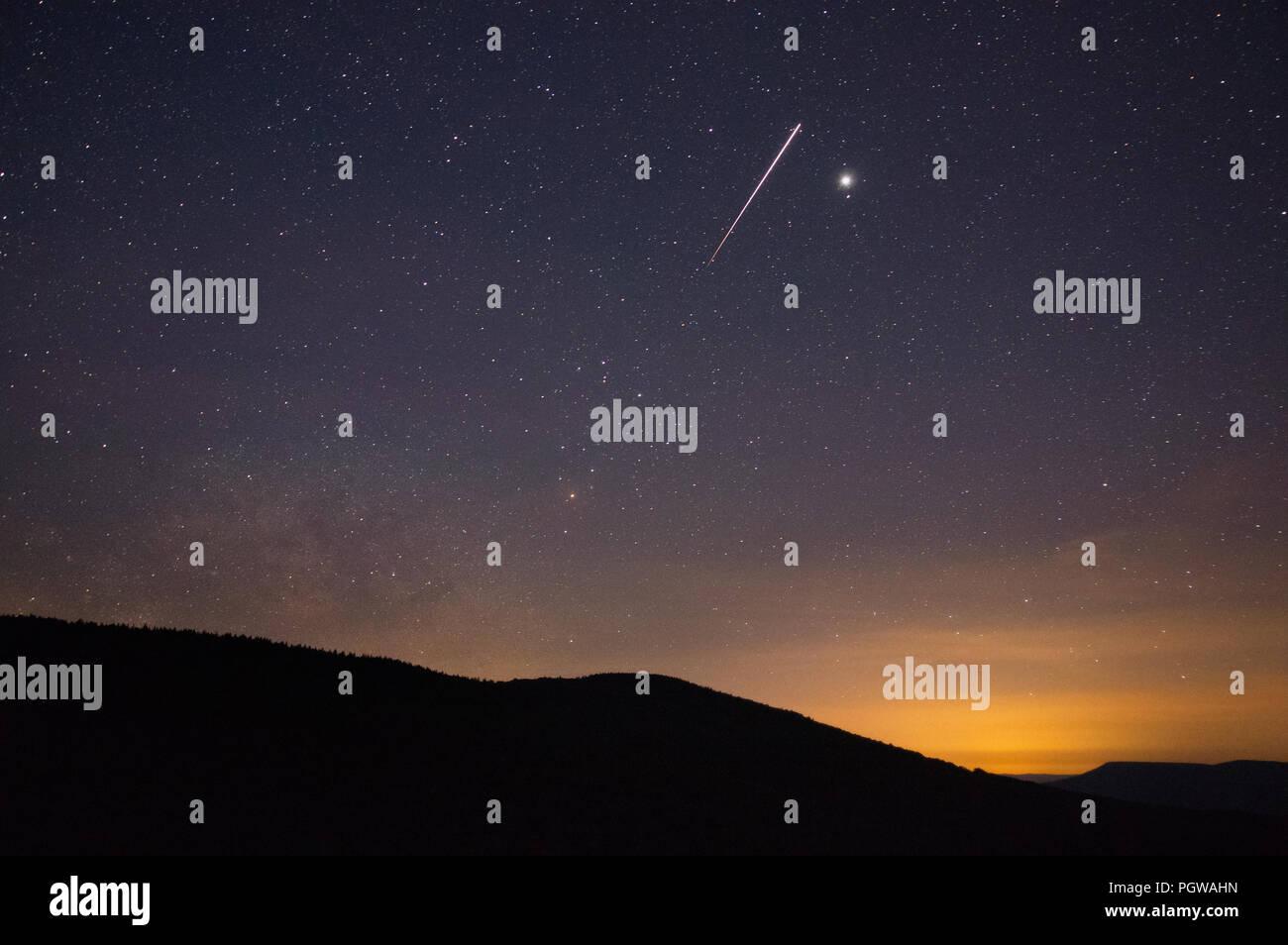 La Station spatiale internationale passe au-dessus de Jupiter comme la Voie lactée commence à s'élever sur les sommets à la fin des heures du crépuscule donnant sur le W Photo Stock