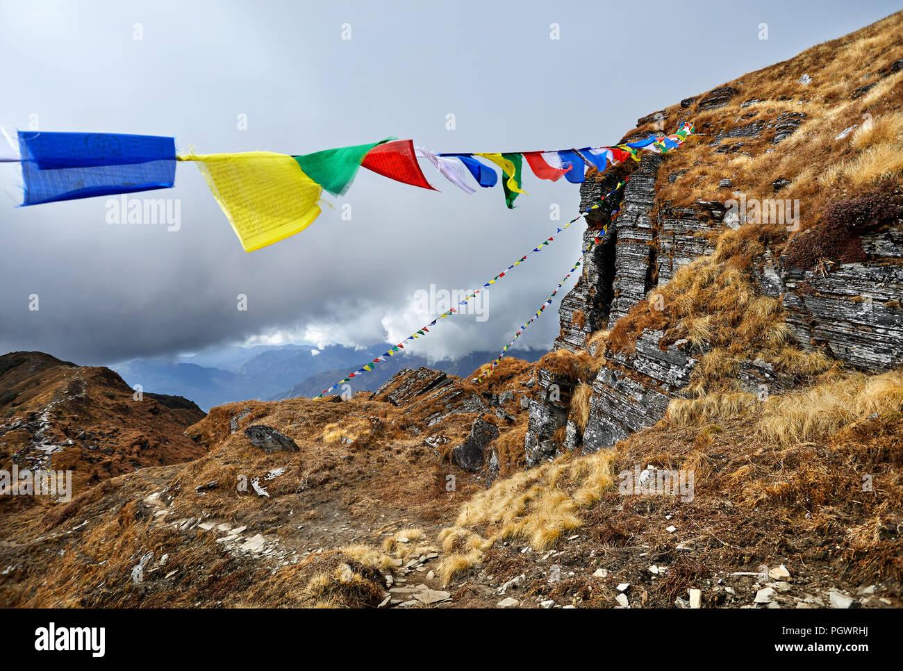 Les rochers et les drapeaux de prière Tibetains Lung Ta au camp de base à l'Himal Mardi Nuageux sommets de montagnes de l'Himalaya au Népal Photo Stock