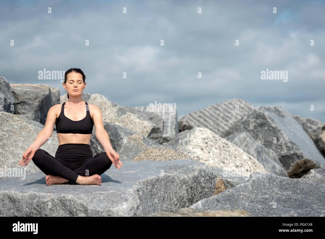 Femme assise méditant à l'extérieur sur les roches, copyspace. Photo Stock