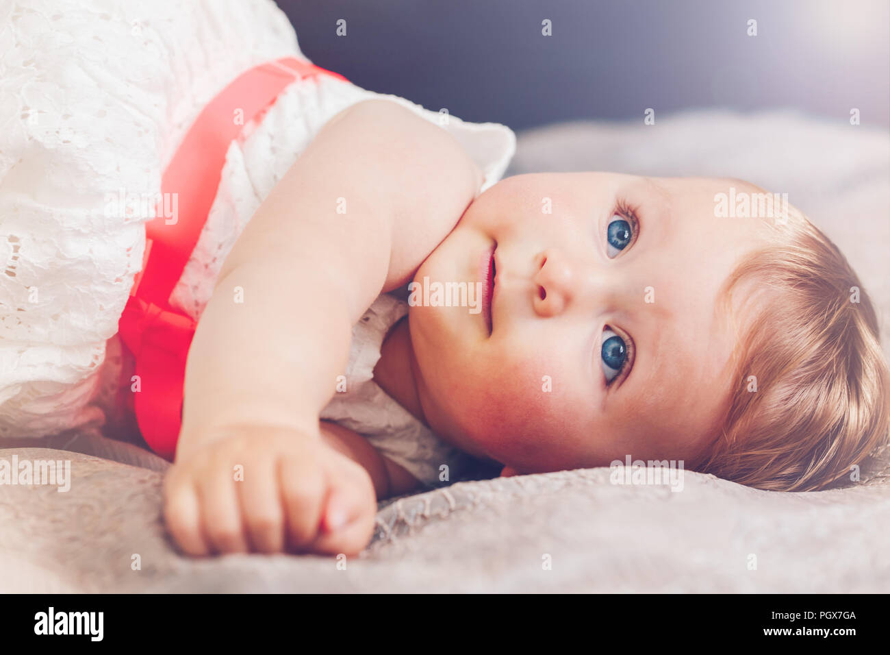 Portrait of cute adorable blonde Woman smiling baby girl l'enfant aux yeux bleus en robe blanche avec red bow lying on bed looking up dreaming, fairy Banque D'Images