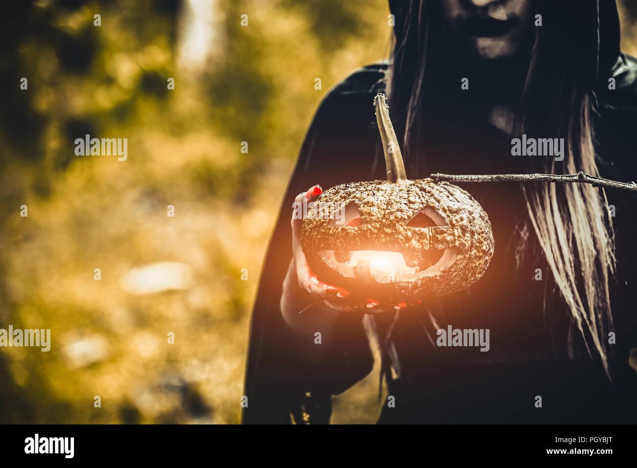 Lanterne citrouille sorcière dans la main. Old woman holding pumpkin en forêt vert foncé. Journée de l'Halloween et le mystère concept. Fantasy de magie thème. L'assistant et M Photo Stock