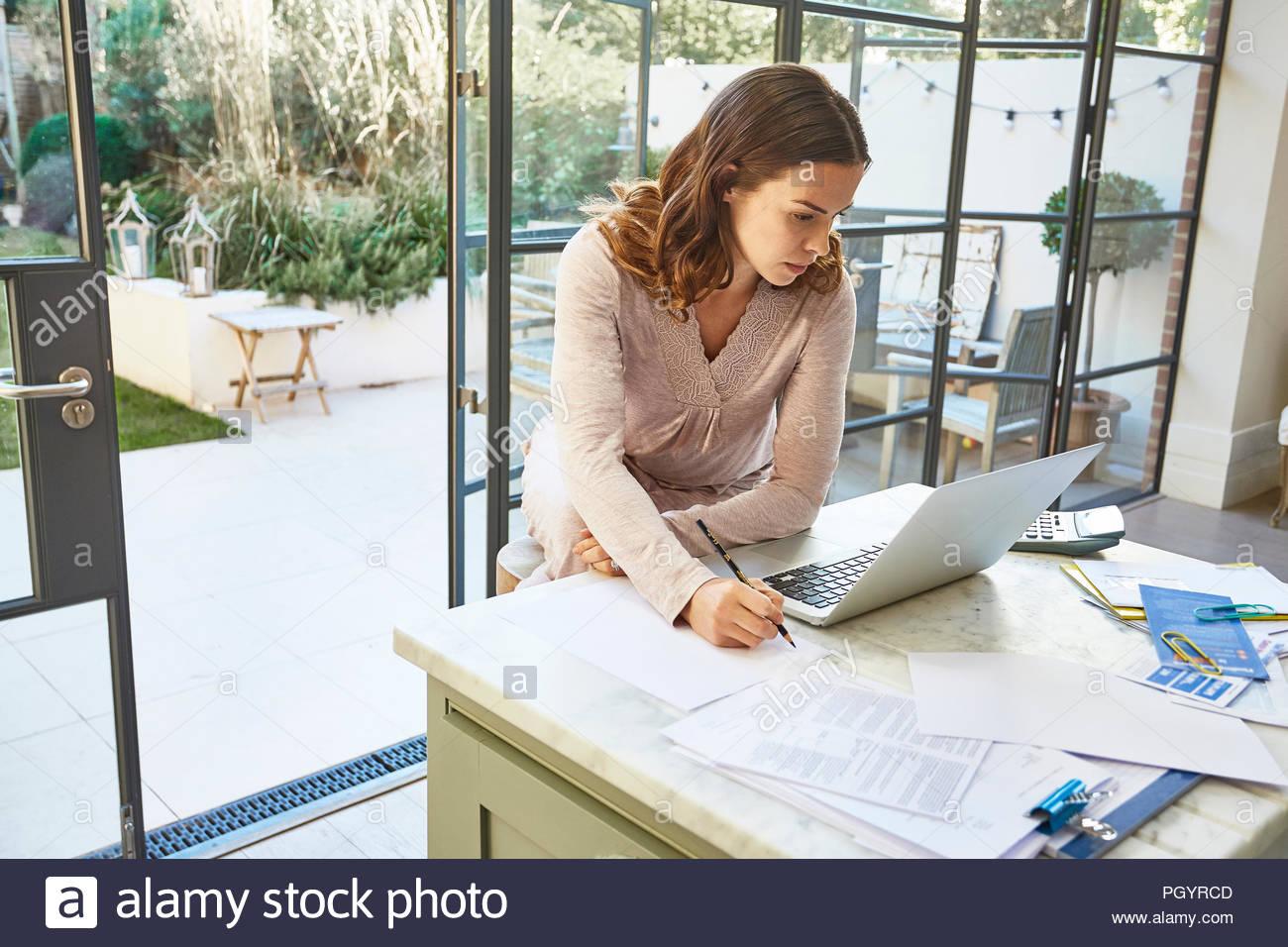 Mid adult woman using laptop au comptoir de la cuisine. Photo Stock