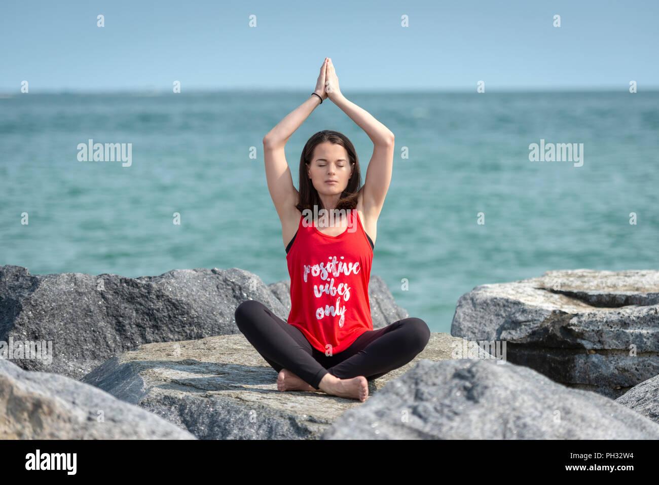 """Femme assise, les jambes croisées sur les roches pratiquant le yoga, pose facile, portant un t shirt avec 'vibes positifs seulement"""" slogan. Banque D'Images"""