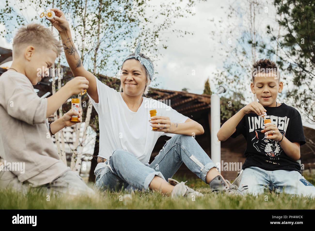 Close up of family blowing bubbles outdoors dans le parc. Photo Stock