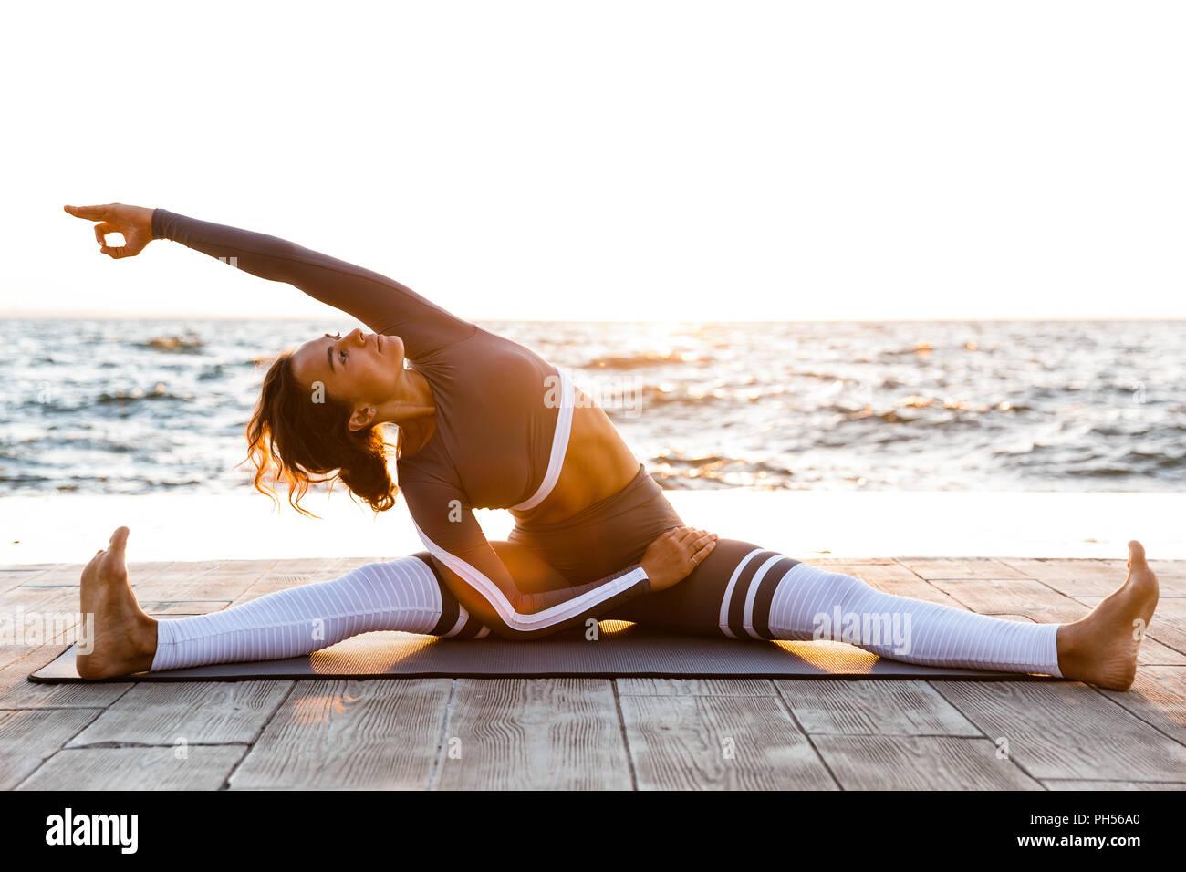 Photo de jeune lady fitness en plein air dans la plage s'étirant les exercices de yoga. Photo Stock