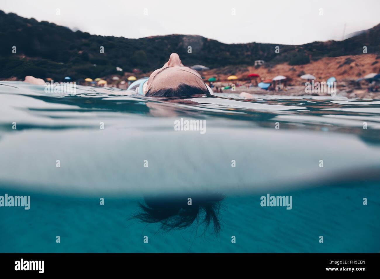 Femme qui reste sur la surface de l'eau avec ses yeux fermés - Détente et méditation concept. Photo Stock
