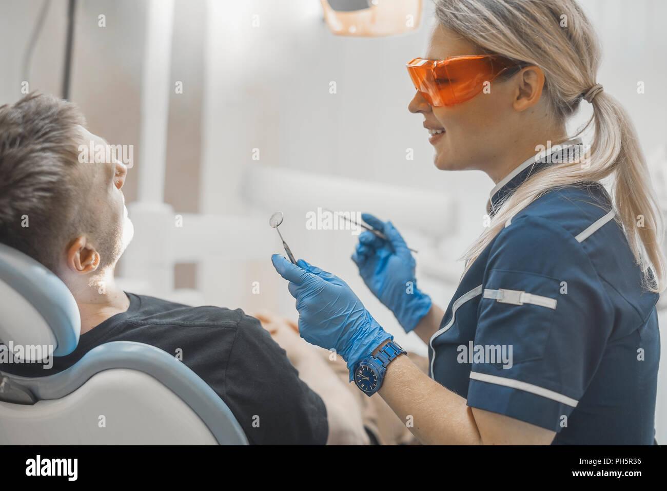 Close up of woman smiling dentiste à un client et en maintenant les instruments dentaires. Photo Stock