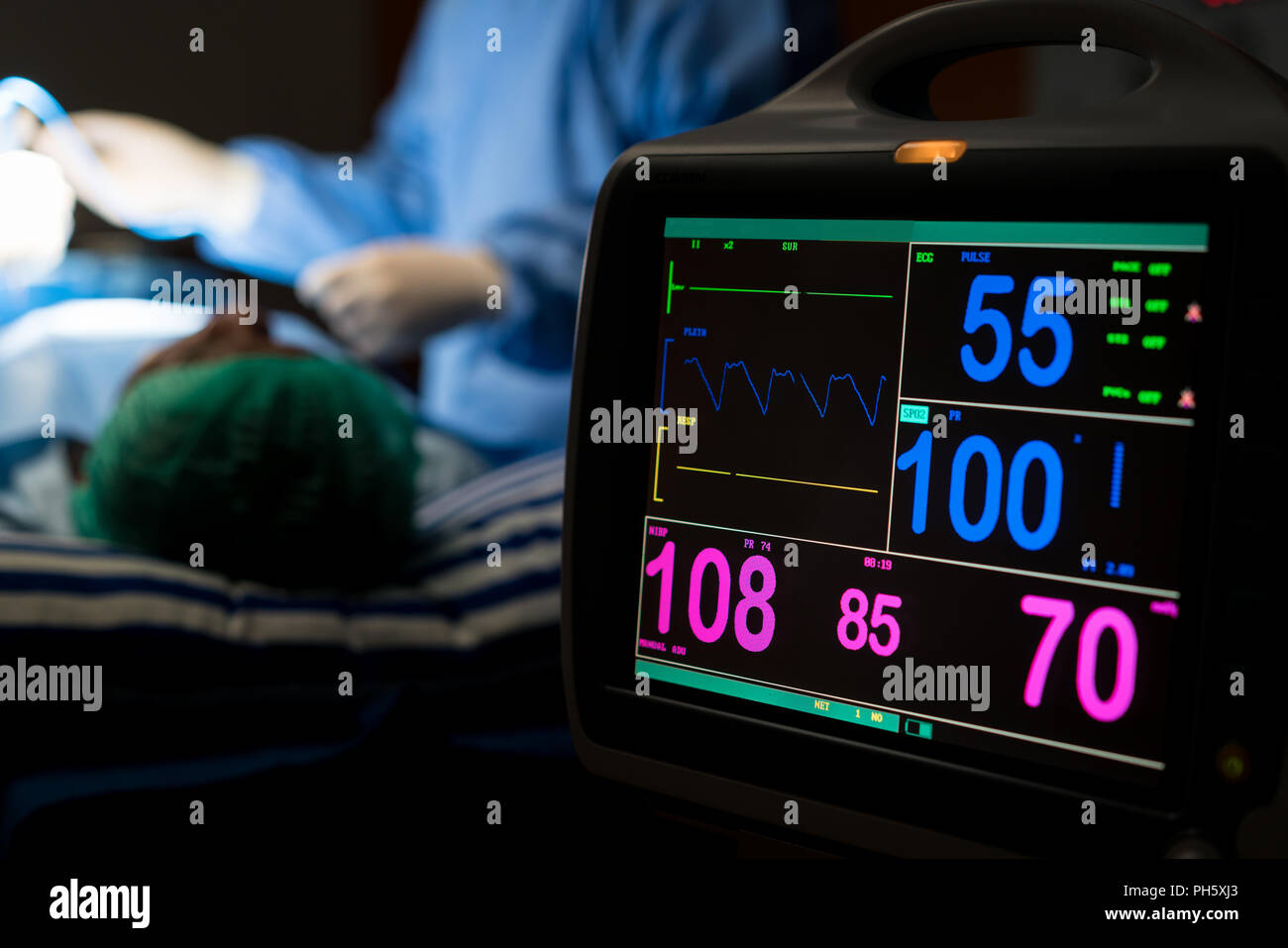 Dans la chirurgie de l'hôpital d'électrocardiogramme à l'urgence d'exploitation montrant la fréquence cardiaque du patient avec l'équipe de chirurgiens de flou en arrière-plan. Santé et medicin Photo Stock