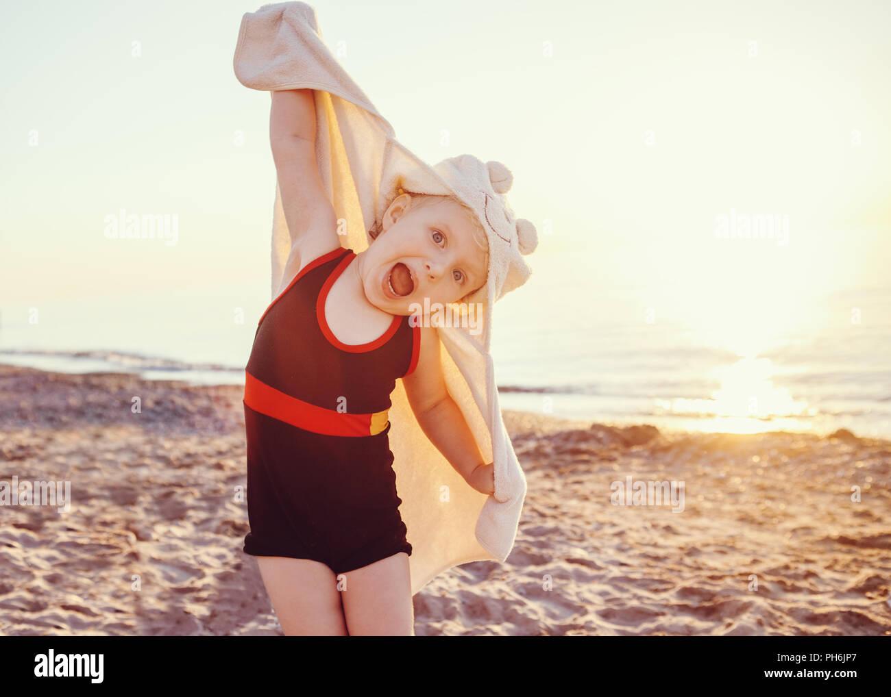 Portrait of cute adorable bambin happy smiling little Girl with towel on beach faire faces pose d'avoir l'amusement, l'expression émotionnelle face, style de su Banque D'Images
