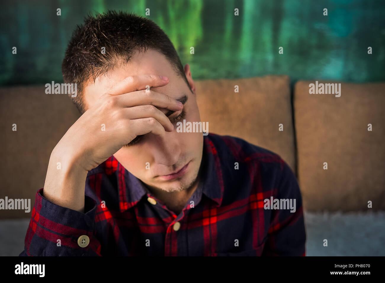 Portrait de jeune homme en colère triste. La couvaison homme assis et tenant une main sur sa tête. Dans une mauvaise humeur. dépression. maux de tête, douleur de tête Photo Stock