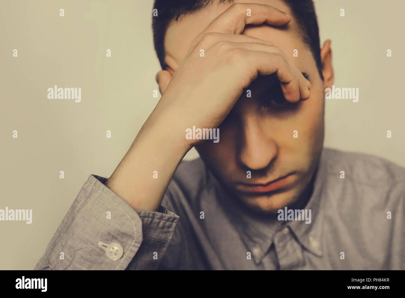La couvaison homme assis et tenant une main sur sa tête. Dans une mauvaise humeur. dépression. maux de tête, la douleur. Jeune homme tire son front, couvrant h Photo Stock