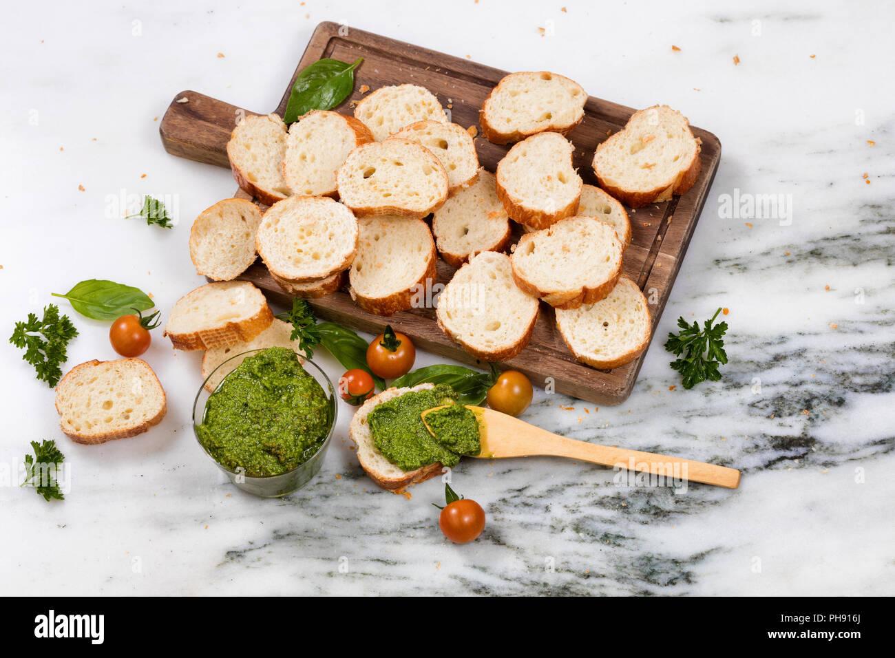 Pesto fraîchement préparés et le pain tranché sur serveur en bois Banque D'Images