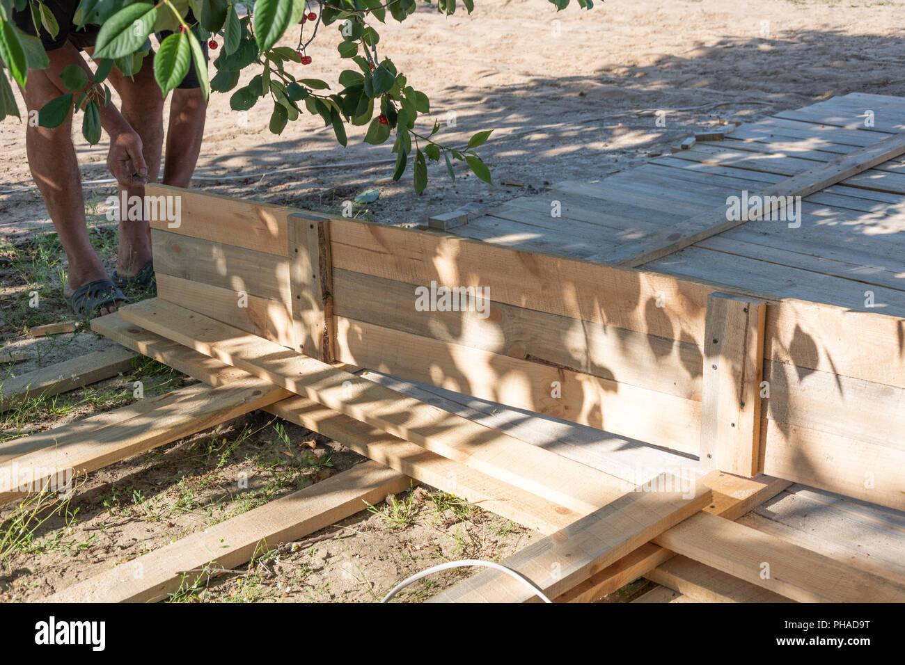 Mur Exterieur En Planche De Coffrage l'homme l'édification d'une clôture en bois. ramasser les