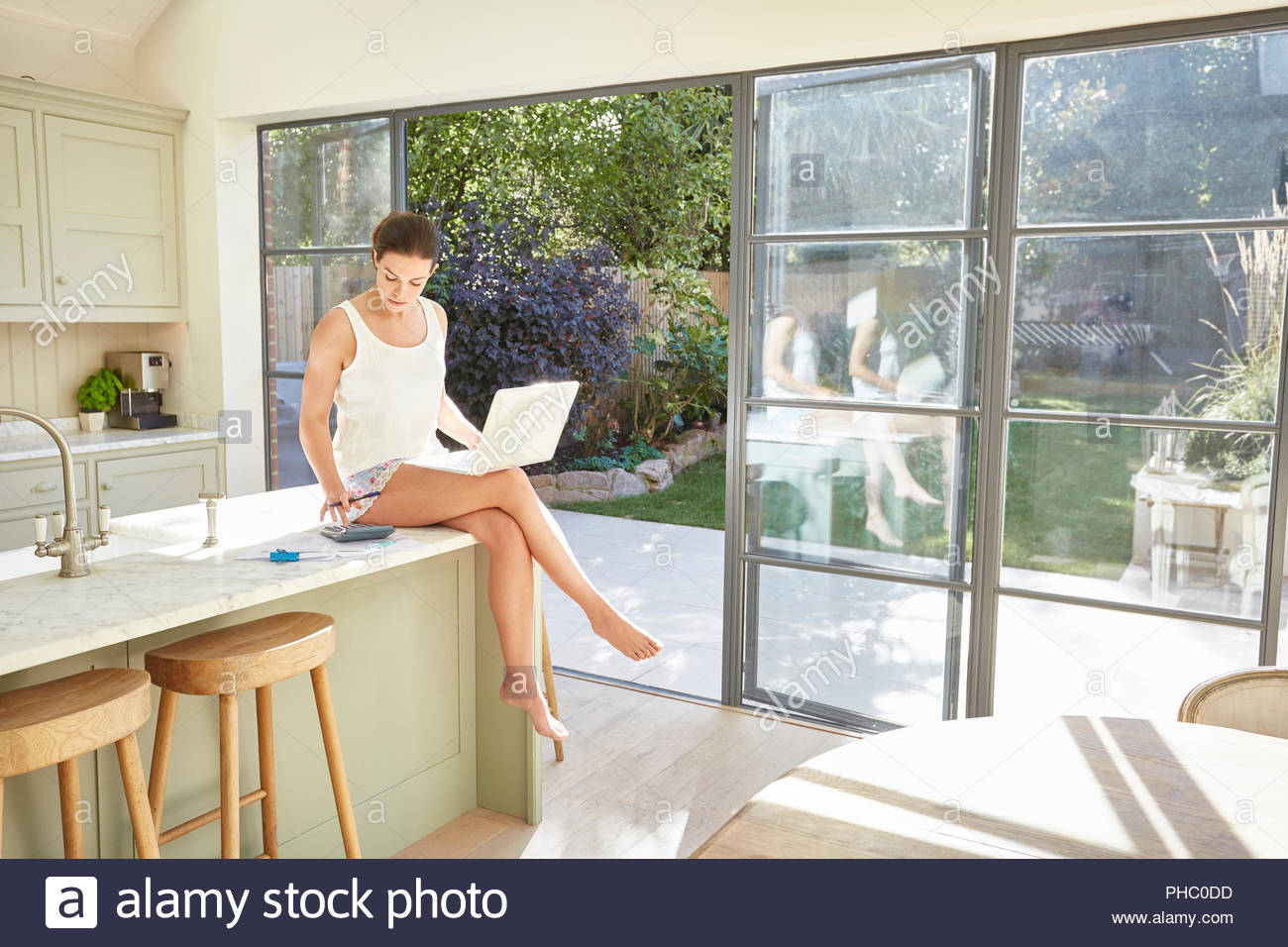 Mid adult woman using laptop. Photo Stock