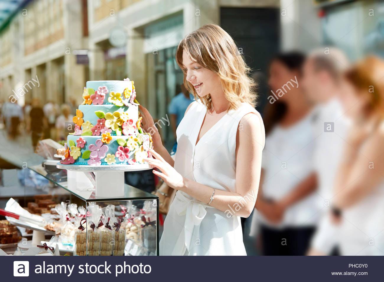 Jeune femme à la recherche de gâteau décoré. Photo Stock