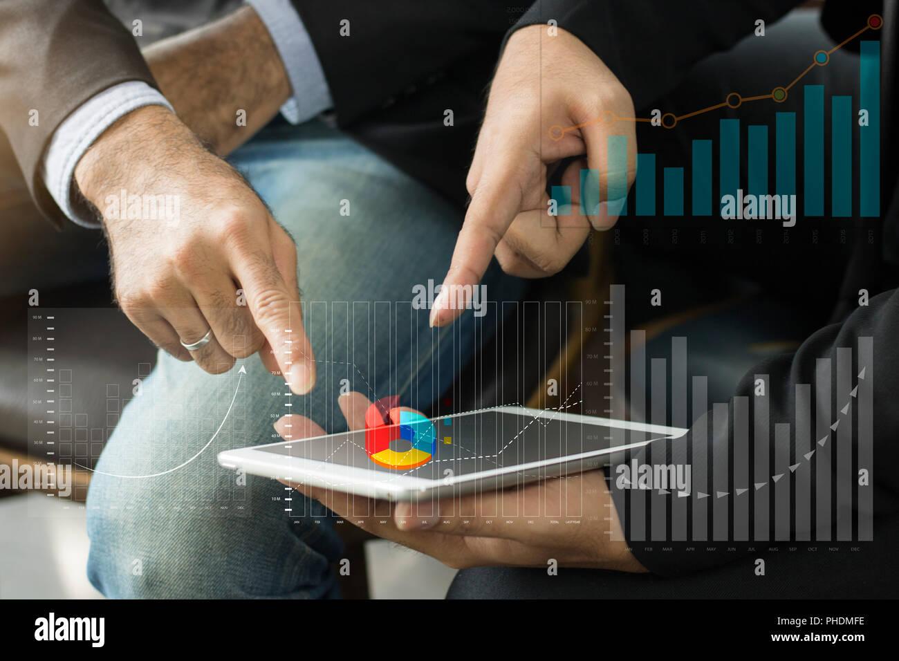 Groupe de gens d'affaires de discuter au sujet de finances de la banque et pointant sur tablette. Photo Stock