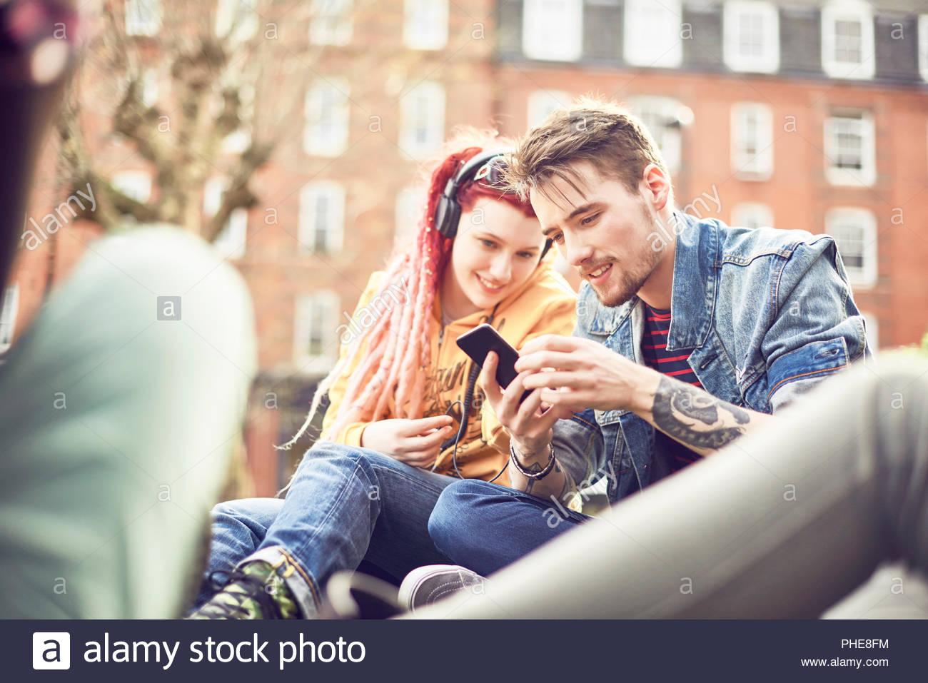 Le partage de la musique couple in park Photo Stock