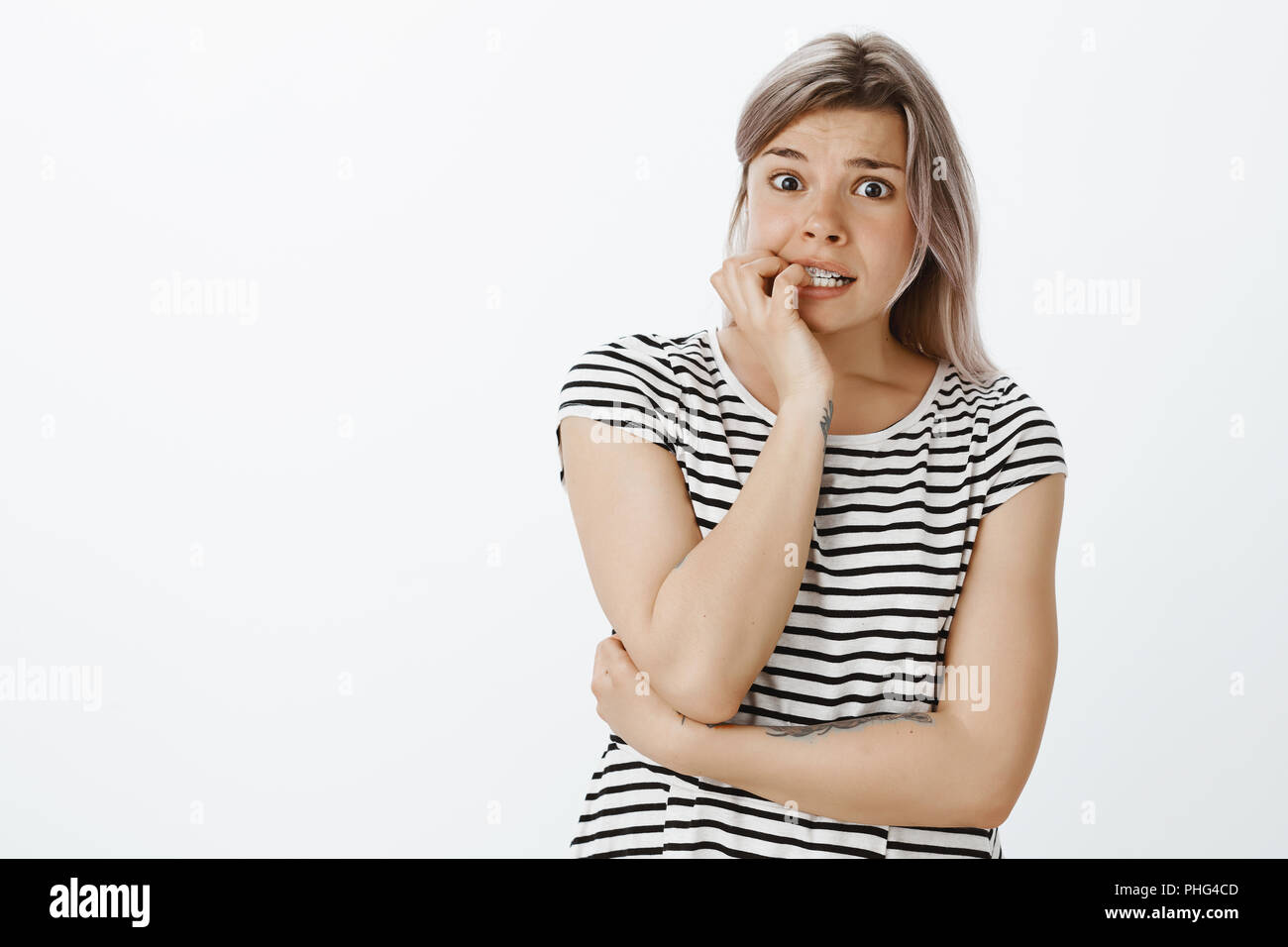 Si ce qu'il sait que c'était moi. Ma copine au nerveux choqué t-shirt à rayures, mordre les ongles et contemplant avec expression effrayée à l'appareil photo, anxiété et peur de répondre de ses erreurs Banque D'Images