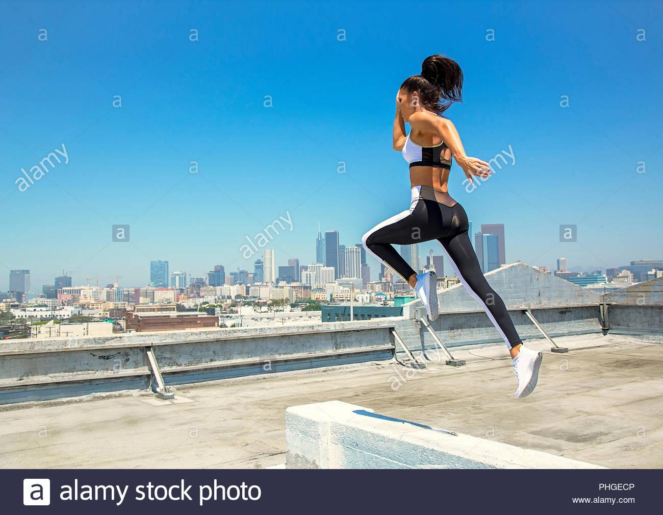 Jeune femme tournant sur faisceau sur le toit Photo Stock