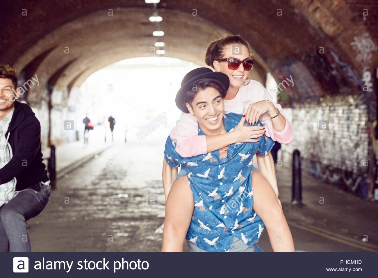 Teenage boy giving girlfriend piggyback ride in tunnel Photo Stock