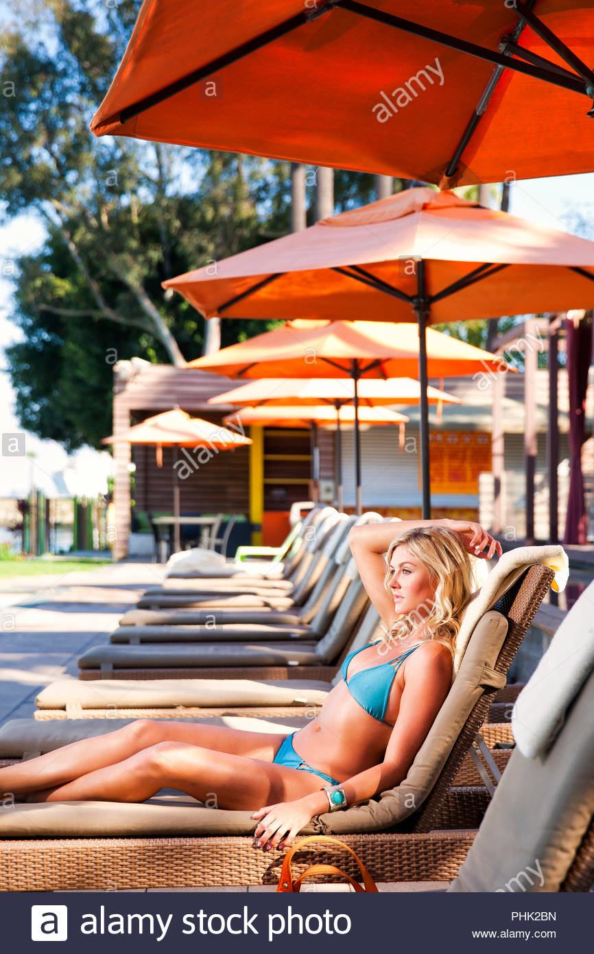 Young woman wearing bikini sur chaise longue Photo Stock
