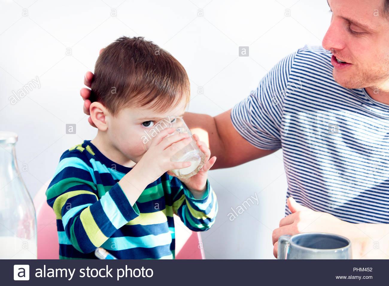 Père avec fils boire du lait Photo Stock