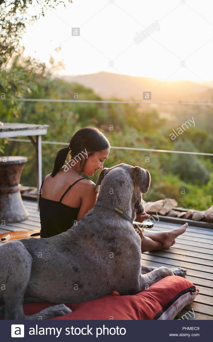 Jeune femme regardant le coucher du soleil avec le chien Photo Stock