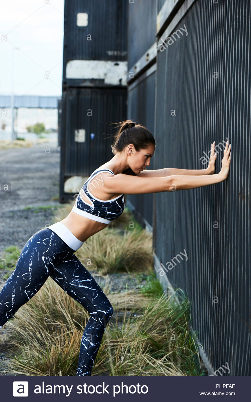 Woman stretching against wall Photo Stock
