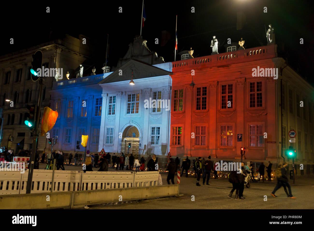 Copenhague, Danemark, 15 novembre, 2015. Des milliers de personnes à Copenhague montrent leur solidarité et sympathie avec le peuple français à l'extérieur de l'Ambassade de France à Copenhague après les attentats terroristes de vendredi dernier à Paris. L'énorme quantité de fleurs et messages pousse encore ce dimanche soir. Kongens Nytorv à Copenhague est éclairé par les couleurs du Tricolore Français projetée sur le bâtiment de l'ambassade française bondé encore après une journée de manifestations officielles et des actions spontanées de sympathie et de solidarité. Banque D'Images