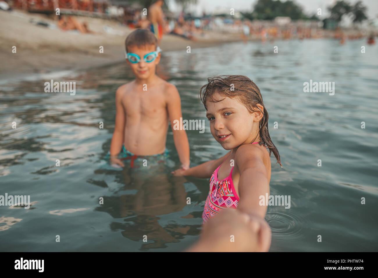Des enfants heureux de jouer dans la mer. Les enfants se tenant la main et inviter leur mère pour aller avec eux. Vacances d'été et d'un style de vie sain concept Photo Stock
