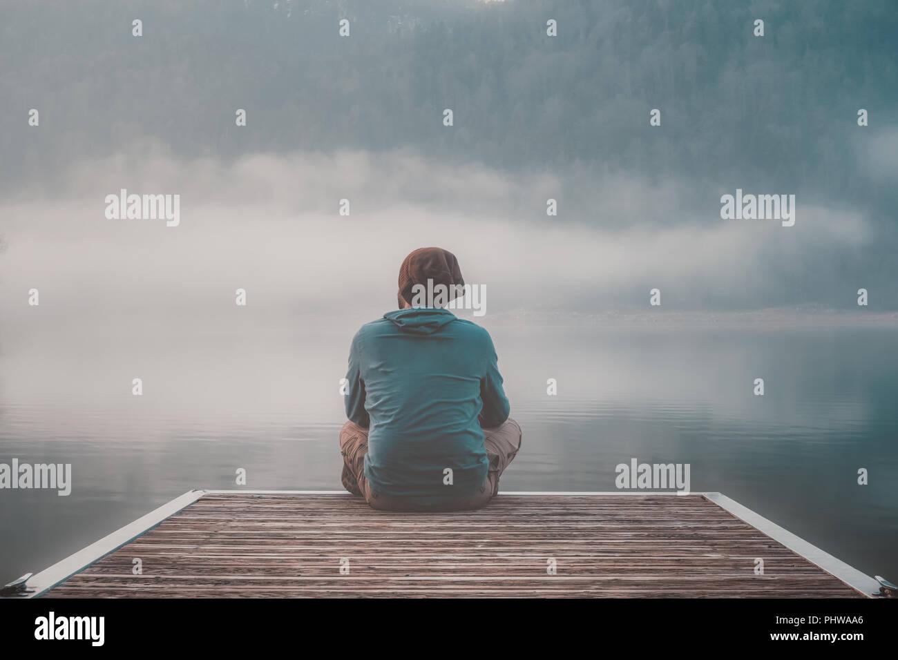 Jeune homme avec capuche assis sur la jetée d'un lac en un jour brumeux. Banque D'Images