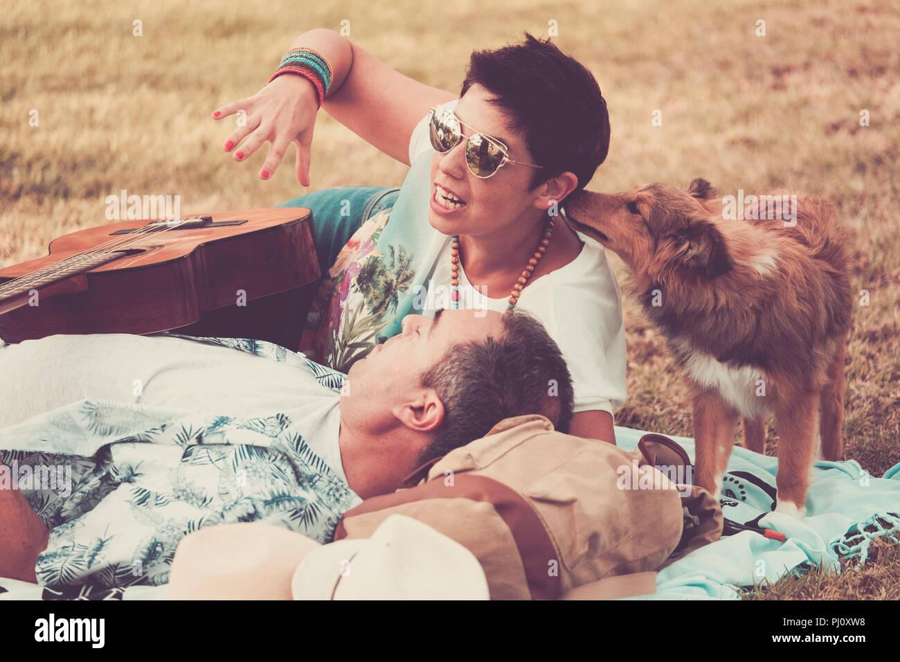 Scène romantique vintage avec jeune belle femme et l'homme s'étendit sur l'herbe profitant du jour. peu jeune animal shetland embrasser un pacifique hippy. Banque D'Images
