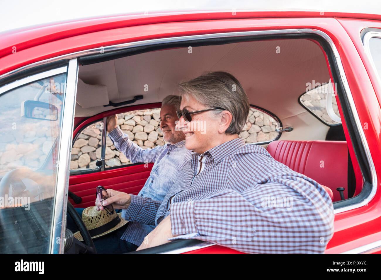 Joli couple hug et de l'amour à l'intérieur d'un vieux millésime rouge voiture garée sur la route. sourit et s'amuser voyageant ensemble. Le bonheur et le mode de vie pour le ni Photo Stock